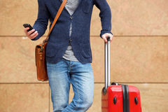 Man standing outdoors with cellphone and travel bag. Cropped portrait of man standing outdoors with cellphone and travel bag Royalty Free Stock Photo