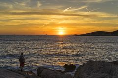 Man standing outdoors at coast looking at sun going down over the sea royalty free stock photos