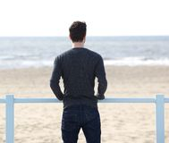 Man standing outdoors looking at the sea. Portrait of a young man standing outdoors looking at the sea royalty free stock photo