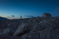 Man standing outdoors on stone rocks at evening in front of small catholic church in Razanj Croatia stock photography