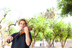 Man standing outside playing violin Royalty Free Stock Image