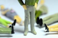 Man standing over lying figures Stock Photos