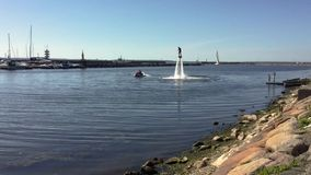 Man standing over the water on flyboard in the yacht harbor stock video footage