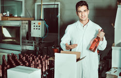 Man standing in packing section on winemaking factory. Glad  diligent man in coat standing in packing section on winemaking factory Royalty Free Stock Photos