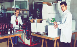 Man standing in packing section on winemaking factory. Glad friendly diligent men in coat standing in packing section on winemaking factory Stock Photo