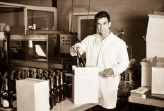 Man standing in packing section on winemaking factory. Glad positive diligent man in coat standing in packing section on winemaking factory Stock Images