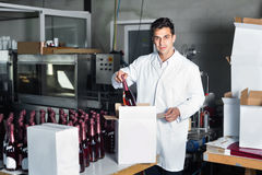 Man standing in packing section on winemaking factory. Glad positive diligent man in coat standing in packing section on winemaking factory Stock Photos