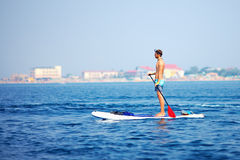 Man standing on paddle board in the sea Royalty Free Stock Photography