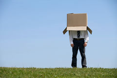Man standing in park with cardboard box over his head Royalty Free Stock Images