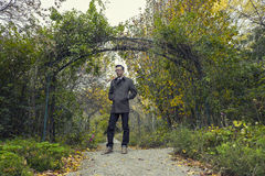 Man standing in park in fall season / autumn. With fall colors on trees and plants stock photography