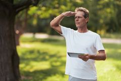 A man is standing in a park with a gray tablet in his hands. He is looking for someone. A man is standing in the park holding his gray tablet. He is looking for Royalty Free Stock Photo
