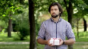 Man is standing in park and holding a present. He shakes it. Man looks to left and right and to his watches on hand stock video