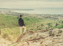 Man standing on peak of mountain and looking at town Royalty Free Stock Image