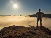Man is standing on the peak of sandstone rock in national park Saxony Switzerland and watching over the morning  misty valley Stock Photo