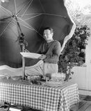 Man standing at a picnic table and holding a plate Royalty Free Stock Photography