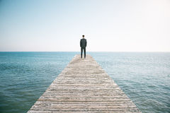 Man standing on the pier and looking into the distance of the oc Stock Photos