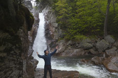 Man Standing in praise in front of Glen Ellis Falls at Pinkham N. Otch in New Hampshire Royalty Free Stock Photo