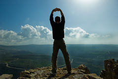 Man standing at the precipice. With rices up hands looking at nice landscape Stock Photography