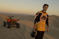 Man Standing By Quad Bike In Desert At Sunset Royalty Free Stock Photos