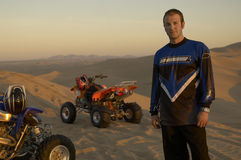 Man Standing By Quadbikes In Desert Stock Photography