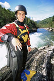 Man standing with raft beside river Stock Photos