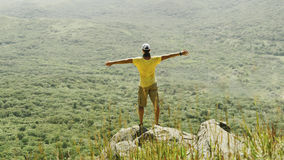 Man standing with raised arms on peak of rock in summer Royalty Free Stock Images