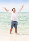 Man standing with raised hands on beach and looking in the sky Royalty Free Stock Photos