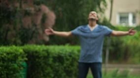 The man standing with raised up hands and closed eyes is enjoying summer warm rain outdoors. stock footage