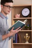Man standing and reading book at study at home. Stock Photography