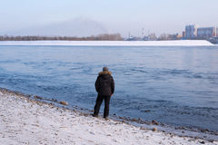 Man standing on a river bank Royalty Free Stock Images