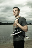 Man standing on the river bank with trainers. Portrait of young man standing on the river bank with trainers Royalty Free Stock Images