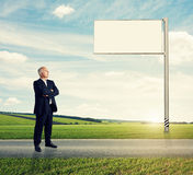 Man standing on the road against billboard Stock Images