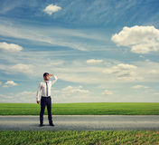 Man standing on road and looking forward Stock Photo