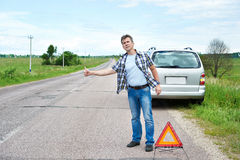 Man standing on road near emergency sign and waiting help Royalty Free Stock Images