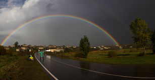 Man standing on the road under rainbow Royalty Free Stock Images