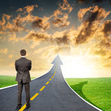 Man standing on roadway going up as arrow Royalty Free Stock Images