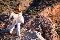 Man standing on rock. Muscular man with tattoo on his back, wearing a white shirt that is dropped down to show his shoulder. He is standing on the edge of a stock image