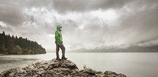 Man standing on a rock beside a mountain lake in rain Stock Images