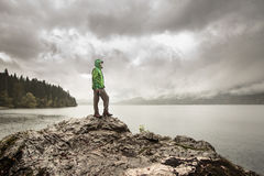 Man standing on a rock beside a mountain lake in rain stock image