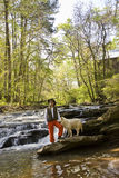 Man Standing on Rock  River  with Dog Stock Images