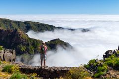 Man standing on rock`s edge above the clouds, Madeira, Portugal Royalty Free Stock Photography