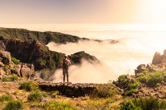 Man standing on rock`s edge above the clouds, Madeira, Portugal Stock Photography