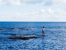 Man standing on rocks fishing. Man dressed in tee shirt and shorts with one hand in a pocket standing on half-submerged rocks fishing in the sea Stock Photos