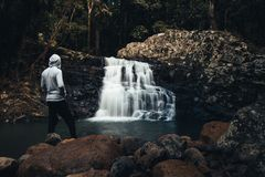 Man standing on rocks with waterfall stock photos