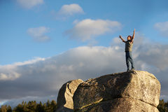 Man standing on rocky outcrop with arms raised Royalty Free Stock Photos