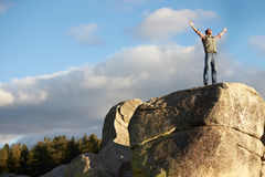 Man standing on rocky outcrop with arms raised Royalty Free Stock Images