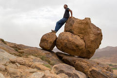 Man standing on round big rocks on the edge of a mountain. Young man standing on round big rocks on the edge of a desert mountain. Man wearing jeans and Royalty Free Stock Photography