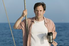 Man standing on sailboat, holding coffee mug Stock Images