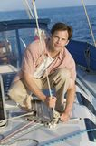 Man standing on sailboat tying rope Royalty Free Stock Image
