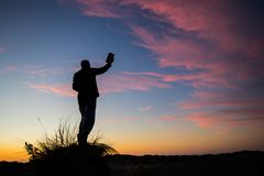 True God Worship. Man standing on a sand hill with holding up The Bible at sunset royalty free stock image
